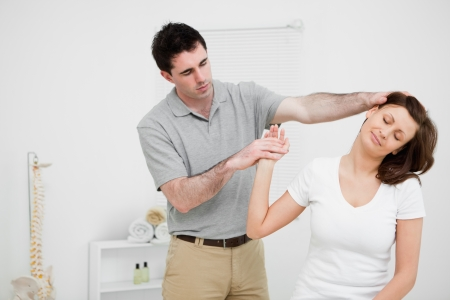 neuromuscular reeducation: Woman being examined her neck by a doctor  in a medical room