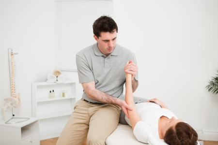 Doctor examining the arm of his patient while touching his elbow in a room Stock Photo - 16203936