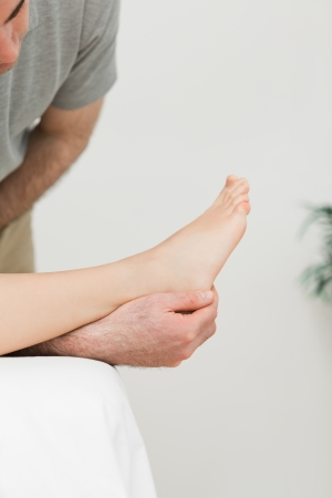 Podiatrist examining the foot of his patient in a room Stock Photo - 16202937