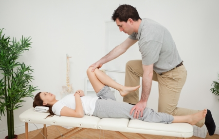 lower limb: Woman being examining her leg by a chiropractor in a medical room