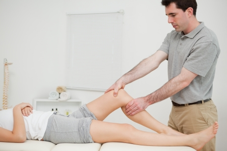 lower limb: Physiotherapist examining the knee of his patient while touching it in a room Stock Photo