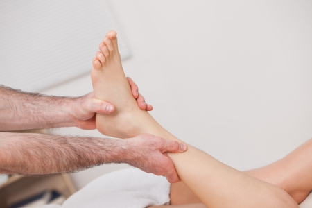 Podiatrist manipulating the ankle of his patient while holding it indoors photo
