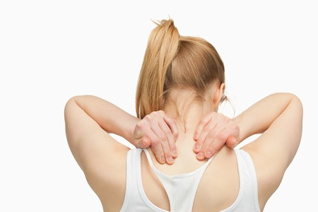Woman massaging her nape with her hands against white background photo