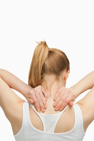 Blonde woman massaging her painful neck against white background photo