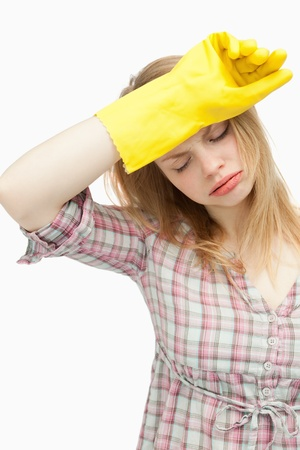 Tired woman wearing cleaning cloves against white background photo
