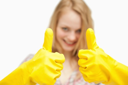 Woman thumbs up while wearing cleaning gloves against white background photo