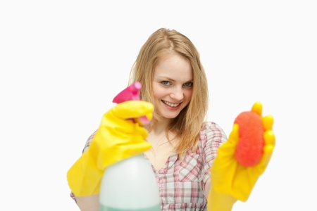 bright housekeeping: Woman holding cleaning agents against white background