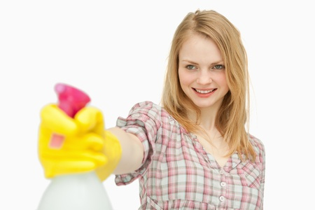 Woman holding a spray bottle while smiling against white background photo