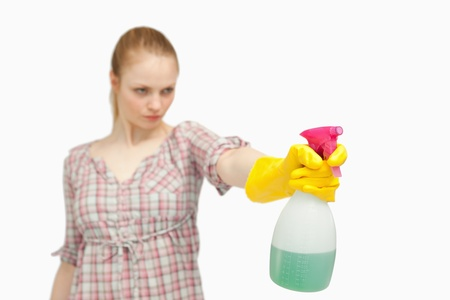 Serious woman holding a spray bottle against white background photo