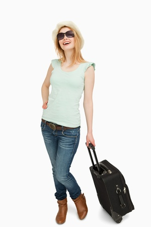 whitebackground: Young woman smiling while holding a suitcase against whitebackground