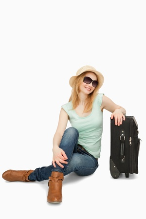 boater: Blonde-haired woman sitting near a suitcase against white background