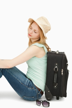 boater: Blonde-haired woman sitting against a suitcase against white background