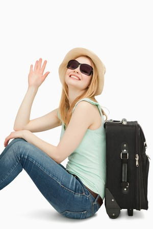 boater: Woman sainsing her hand while sitting near a suitcase against white background