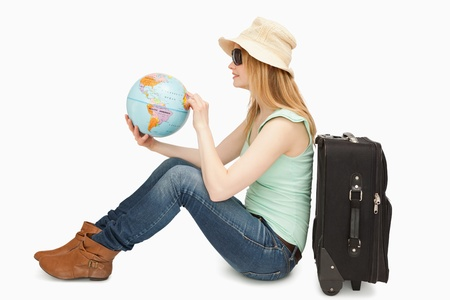 Woman holding a world globe while sitting against white background photo
