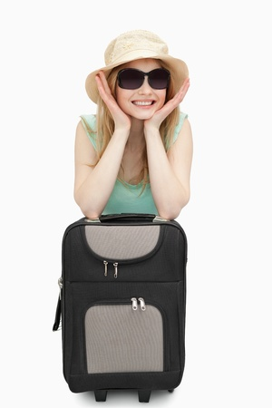 boater: Cheerful woman leaning on a suitcase while sitting against white background