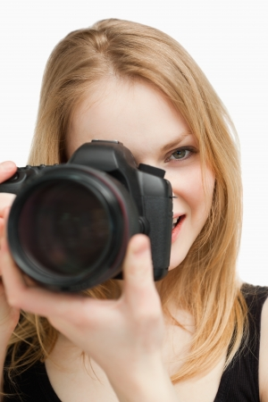Blonde woman aiming with a camera against white background photo