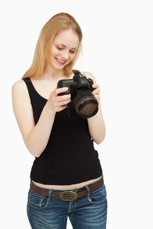 Woman looking at the screen of her camera while smiling against white background Stock Photo - 18682713