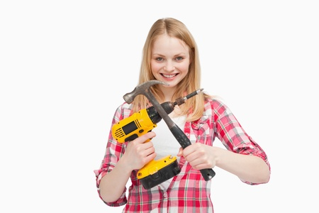 Woman holding an electric screwdriver and a hammer against white background photo