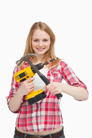 Young woman holding tools against white background photo