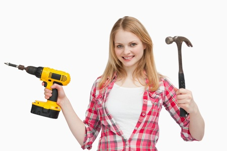 Smiling woman holding tools against white background photo