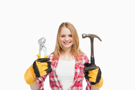 Woman holding tools while smiling against white background photo