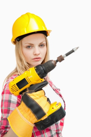 Serious woman holding an electric screwdriver against white background photo