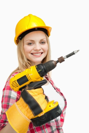 Woman smiling while holding an electric screwdriver against white background photo