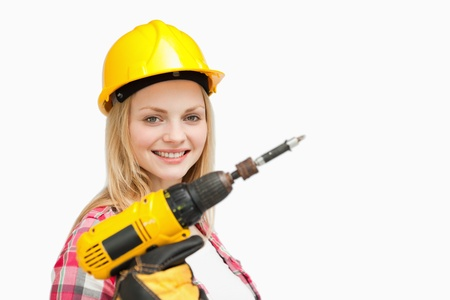 Woman holding an electric screwdriver while smiling against white background photo