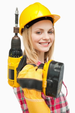 Smiling woman holding an electric screwdriver against white background photo
