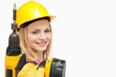 Young woman holding an electric screwdriver against white background photo