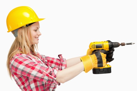 Woman using an electric screwdriver against white background photo
