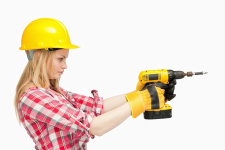 Serious woman using an electric screwdriver against white background photo