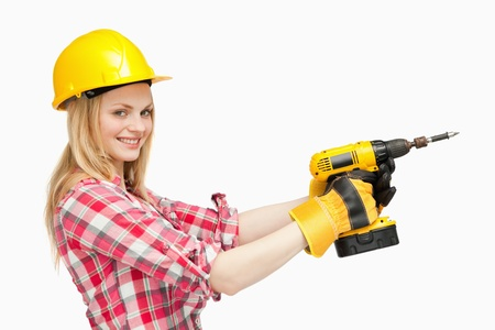 Smiling woman using an electric screwdriver against white background photo