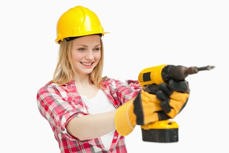 Joyful woman using an electric screwdriver against white background photo