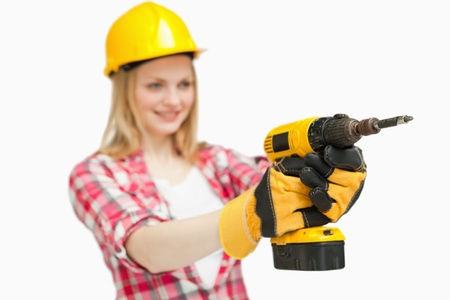 Cheerful woman using an electric screwdriver against white background photo