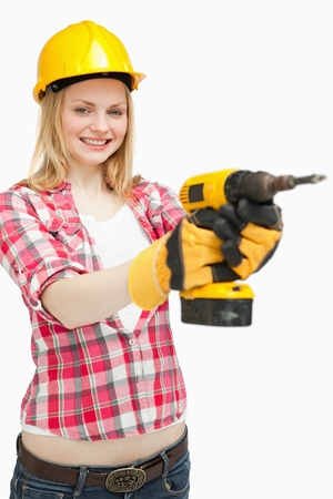 Woman using an electric screwdriver while smiling against white background photo