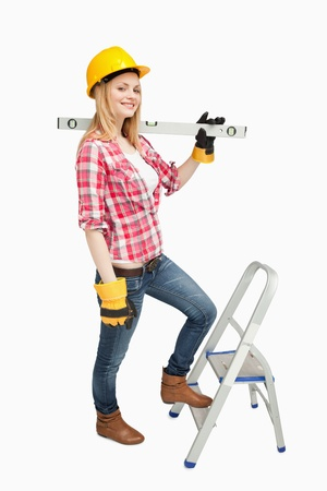 step ladder: Woman holding a spirit level next to a step ladder against white background Stock Photo