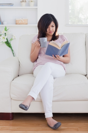 Woman reading a book while holding a mug on a sofa photo