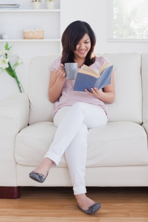 Woman reading a book while sitting on a couch in a living room photo