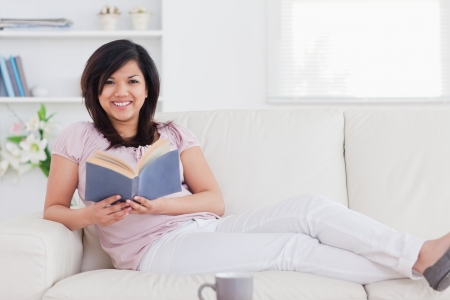 Woman lying on a sofa and holding a book in a living room photo