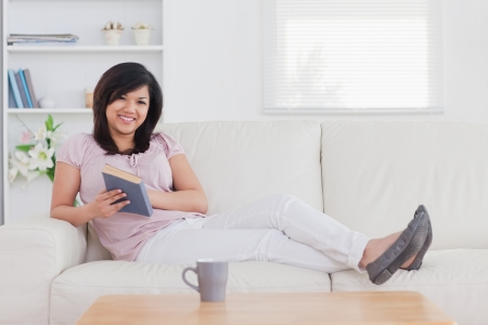 Smiling woman lying on a sofa in a living room photo