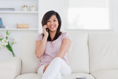 laughing woman holding a phone and sitting on a couch photo