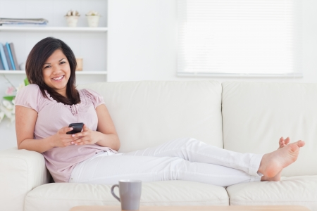 Woman smiling and lying on a couch in a living room photo