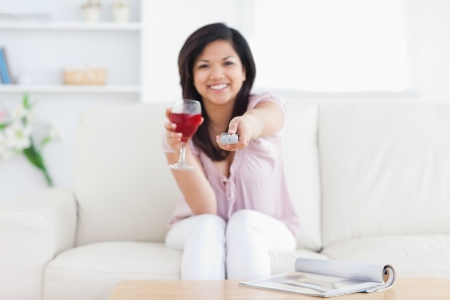 Woman sitting in a white couch while holding a glass of red wine and a television remote in a living room photo
