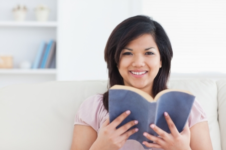 Woman smiling while holding a book in a living room photo