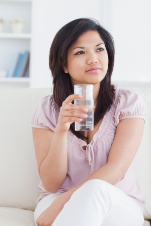 Woman sitting on a couch while crossing her legs and holding a glass of water in a living room photo
