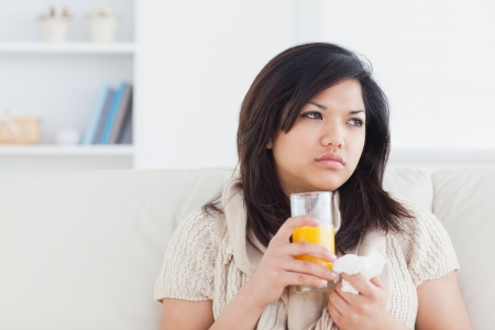 Sick woman holding a glass of orange juice in a living room photo