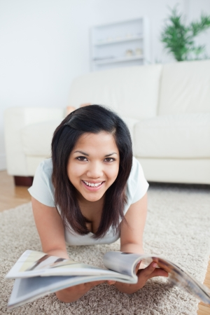 Woman laying on the floor and smiles as she holds a magazine in a living room photo