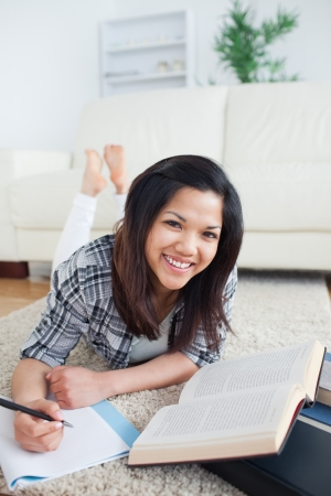 Smiling woman with a book and a notebook photo
