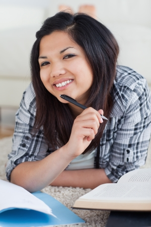Smiling woman holding a pen as she lays on the floor in a living room photo